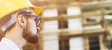 עובד בניין עם קסדת בטיחות צופה על אתר הבניה