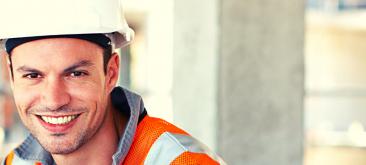 עובד בניין חובש קסדת בטיחות מחייך